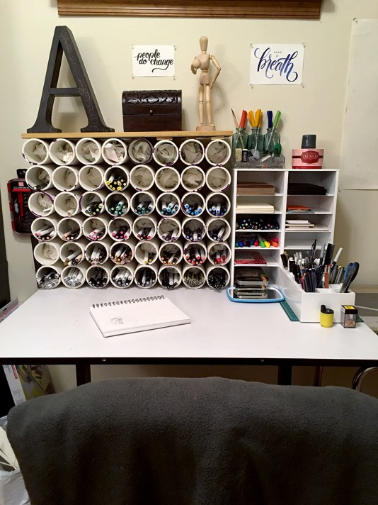 A white drawing desk lies flat, with most of the surface open for drawing. The rest of the surface is covered with a PVC pipe marker organizer filled with art markers, a mini-shelf unit filled with lettering supplies and small sheets of paper, an organizer with all my drawing supplies, and apothecary bottles housing my fountain pens.