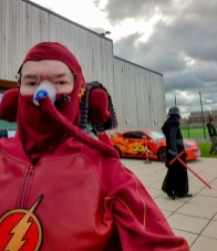 Geekmania Gloucester Daniel Baker dressed as The Flash in front of Darth Maul and a car from Cars