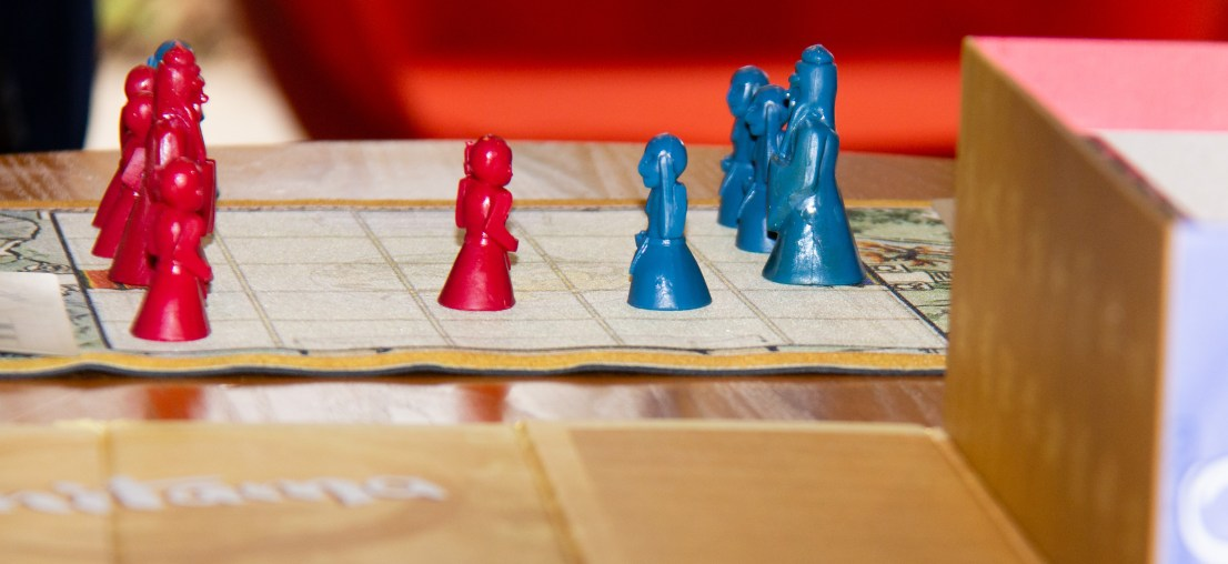 Close up of red and blue boardgame pieces at DMD Pathfinders Christmas Party held at Helen and Douglas House