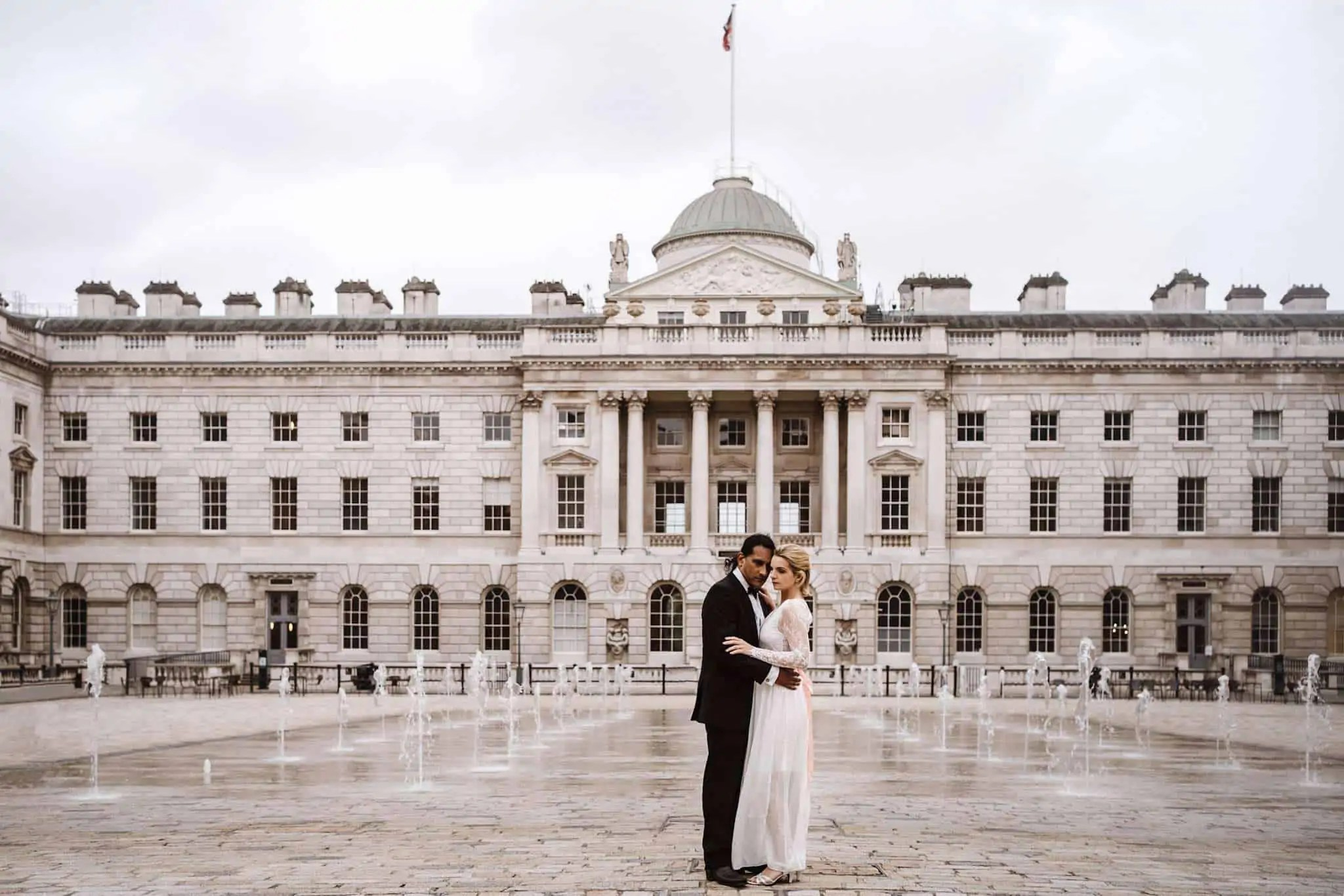 A bride and groom posing in front of Somerset House