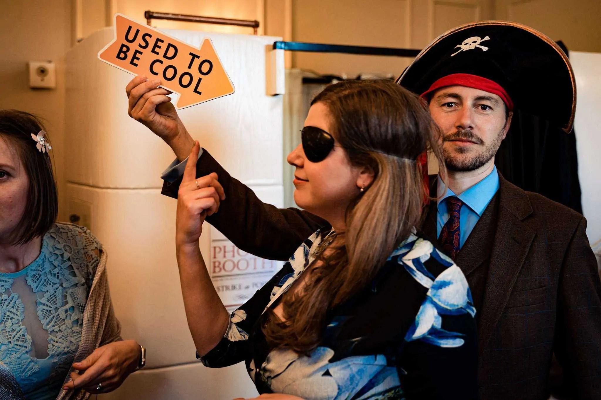 A funny picture at a wedding in Hampshire of a man holding a 'used to be cool' sign