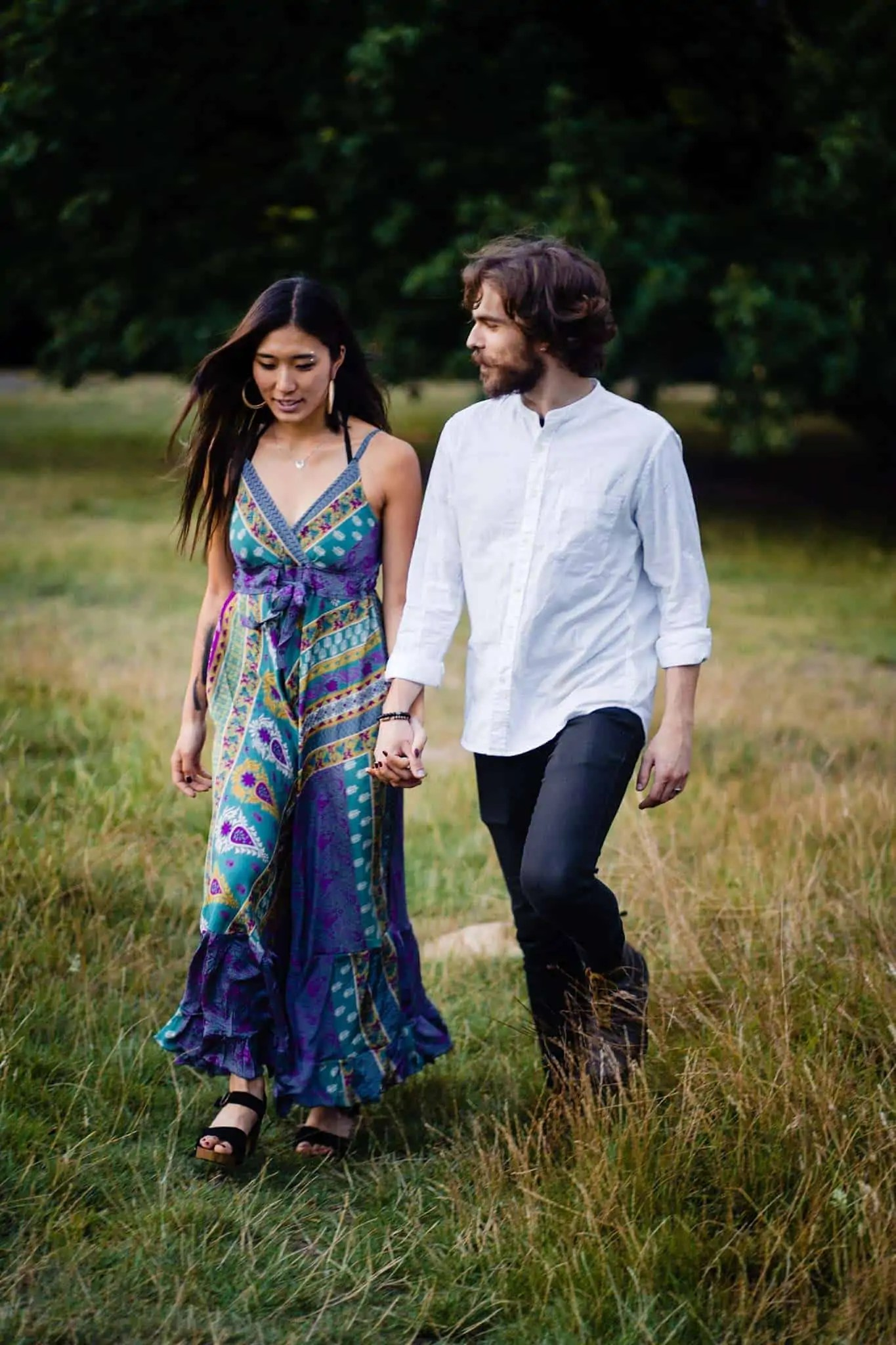 An engaged couple walking through Hampstead Heath on an engagement shoot