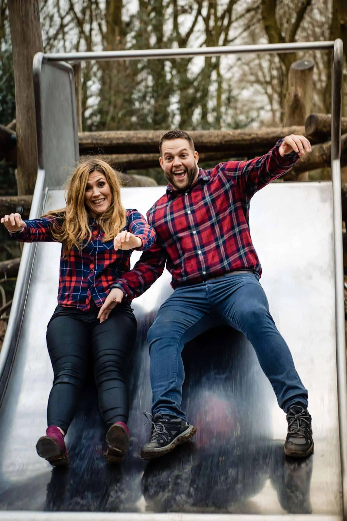 An engaged couple having fun on a slide during an engagement shoot
