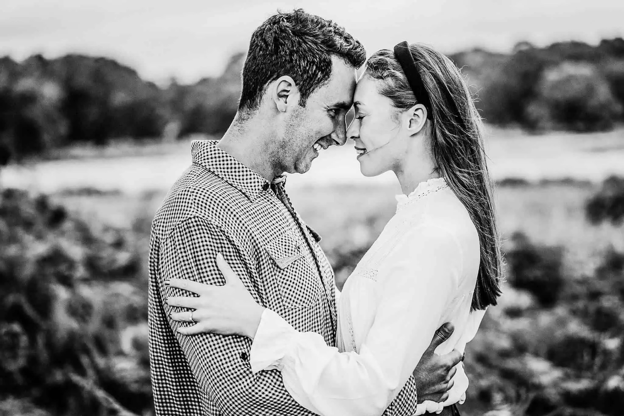 An engaged couple looking into each others eyes in Richmond Park