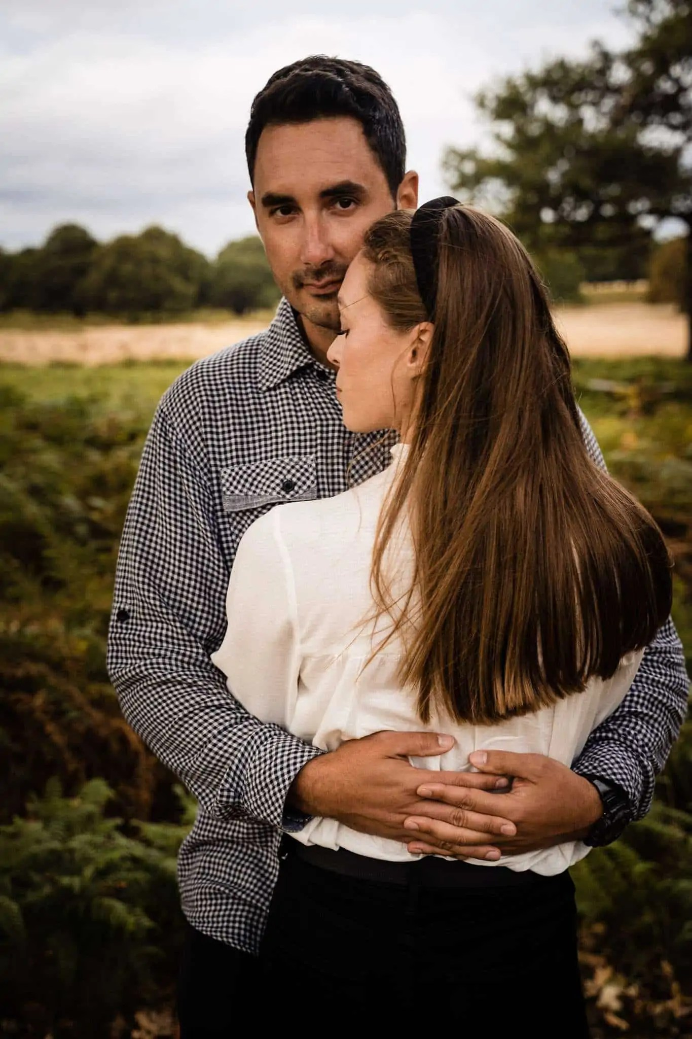 An engaged couple embrace during an engagement shoot in Richmond Park