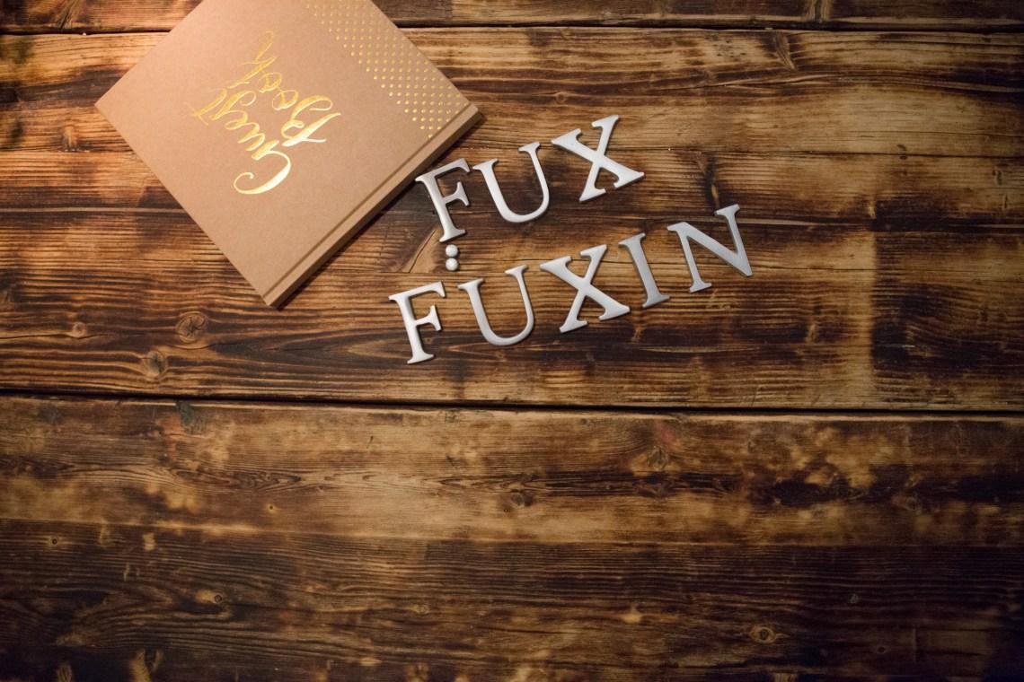 Buch und Buchstaben auf einem Holztisch mit dem Studionamen Fux und Füxin