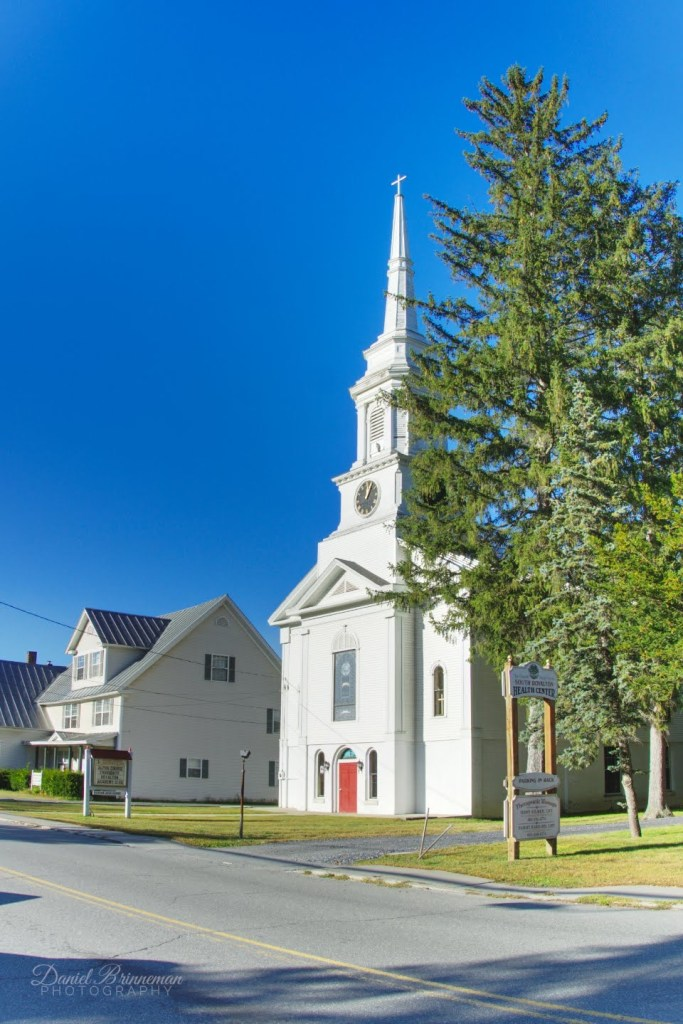 Red Door Church in South Royalton, Vermont, has a tall white steeple and a red door with stained glass windows, Balsam Fir as tall as the steeple in front and to the right side of it, the building is all white