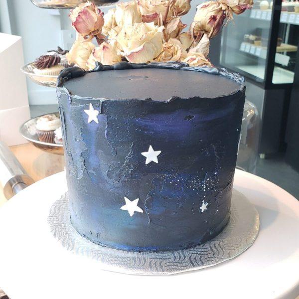 Gâteau galaxie avec couleur noir, blue, mauve et blanc.