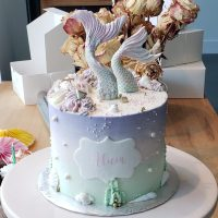 Gâteau en crème au beurre à la vanille, decore avec couleur vert, rose et mauve pâle avec queue de sirène en pâte à sucre.
