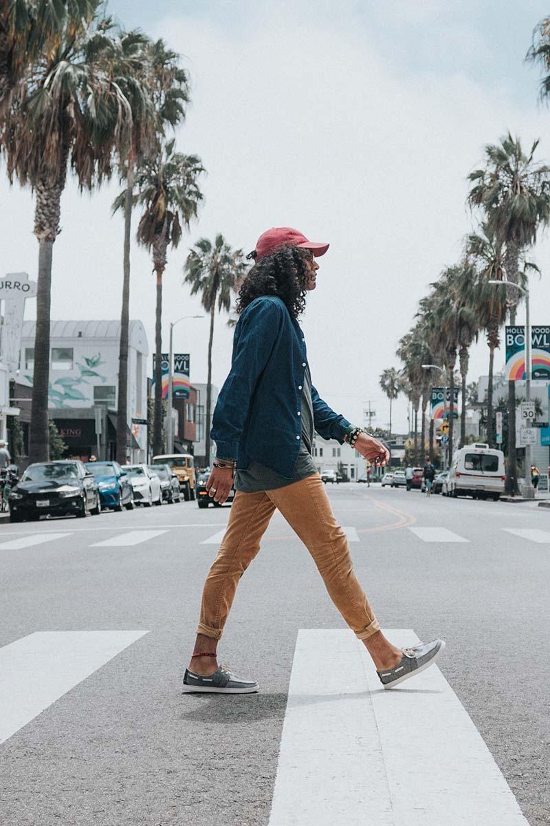 Pessoa vestindo blusa jeans,  calça na cor caramelo e usando boné vermelho. Ela está atravessando a rua