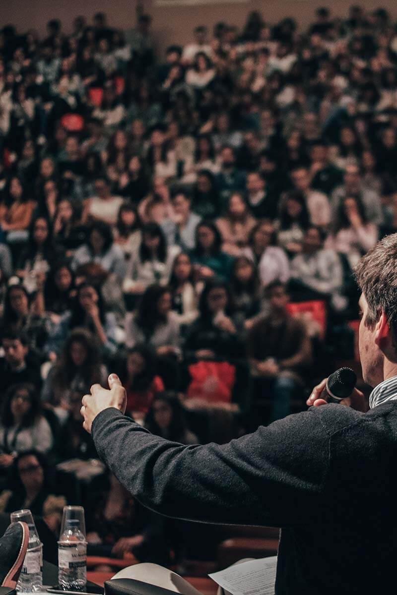 A imagem mostra alguém discursando para uma grande plateia