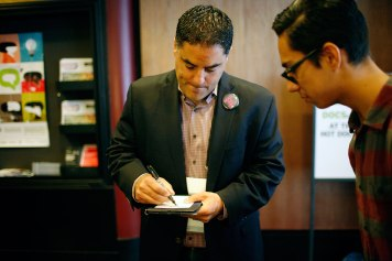 """Media personality Cenk Uygur signs an autograph for a fan after a screening of """"Mad As Hell"""" at the Bloor Cinema"""