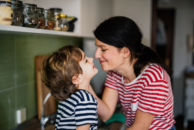 Foto com mulher e criança, um de frente para o outro, bem próximos, sorrindo.