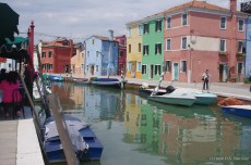 Brightly colored buildings reflect in a canal in Burano