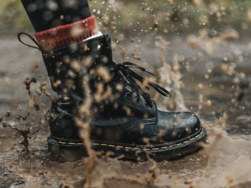 black boot stepping into a brown mud puddle