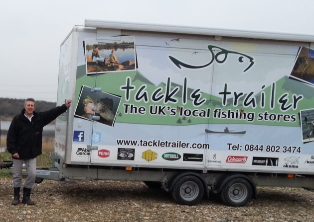 Man stands beside trailer advertising tackle shop