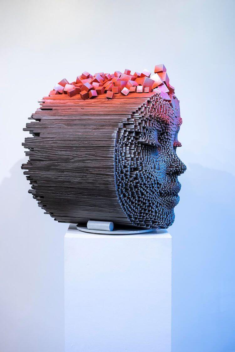Pixelated wooden faces express the human spirit