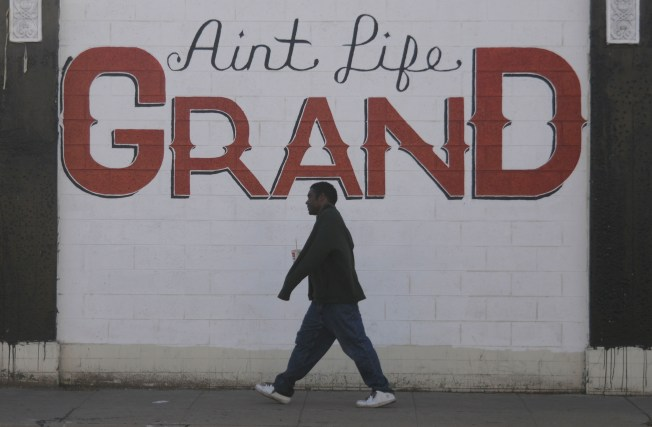 A man walks by a mural on the outside wall of art gallery Legend City Studios along Van Buren Street near Grand Avenue on Wednesday, Oct. 6. The art gallery has several murals painted on its walls by different artists downtown. (Photo by Danika Worthington)