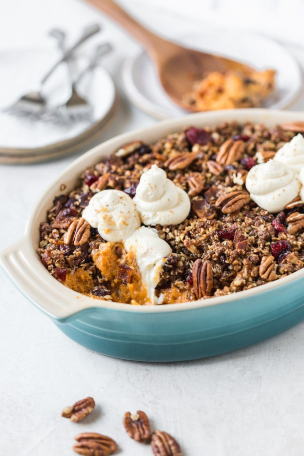 A delicious, creamy sweet potato casserole topped with pecan, dried cranberry, and bacon crumble and whipped goat cheese.
