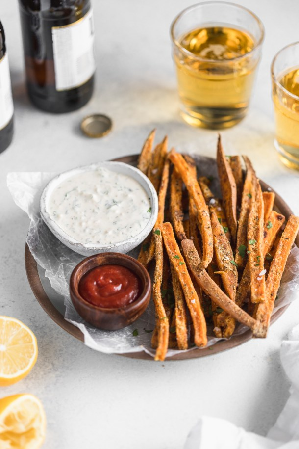 Side view shot of baked sweet potato fries with ranch dipping sauce and cold beer.
