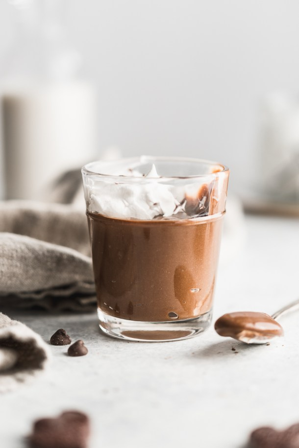Cup of creamy dark chocolate pudding topped with coconut whipped cream with a spoonful on the side.