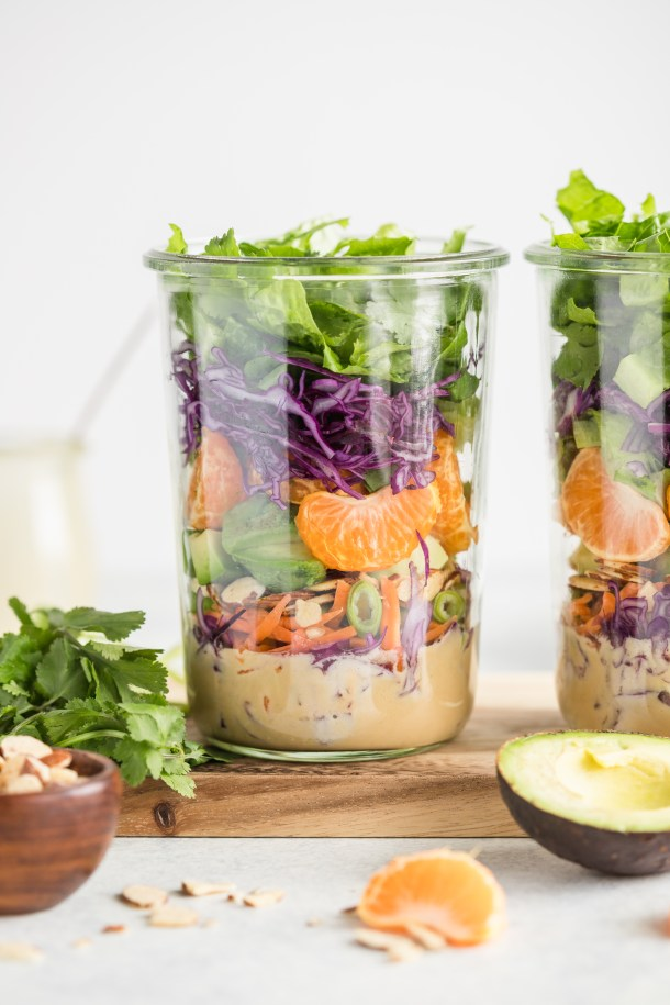 1 large clear jar filled with romaine lettuce, red cabbage, carrots, mandarin oranges, avocados, almonds, and cilantro with a tahini miso dressing.