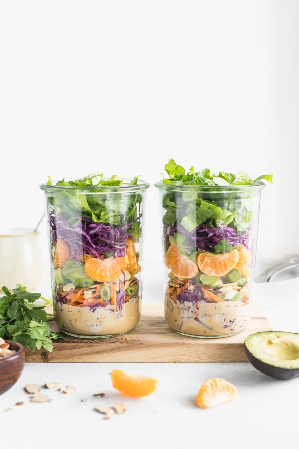 2 large clear jars filled with romaine lettuce, red cabbage, carrots, mandarin oranges, avocados, almonds, and cilantro with a tahini miso dressing.