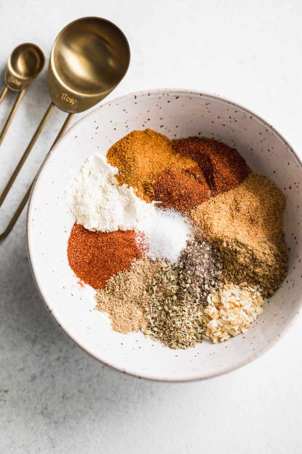 A overhead shot of a bowl of a spice blend of chili powder, cumin, garlic powder, onion powder, dried oregano, smoked paprika, dried coriander, and salt and pepper with 2 gold measuring spoons.