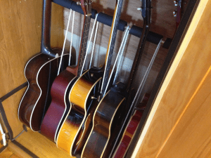 """Guitars rest against rubber water pipe insulation around copper pipes. 1/4"""" nylon cord separates guitars."""
