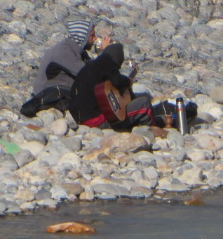 A couple of El Chalten residents playing music by the river