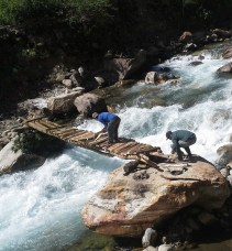 Men replacing a washed out foot bridge