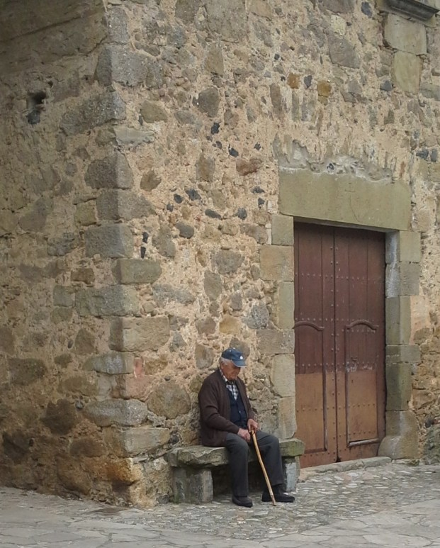 Man on a bench by a door