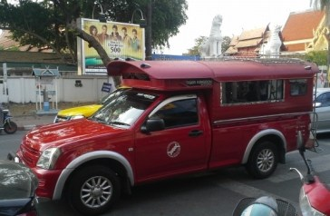 Red top taxi. You tell the driver where you want to go. He quotes you a price. You climb in the back. The driver may stop for other passengers, and drop them off, so you don't really know when you will arrive but it is cheap.