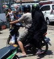 A woman in full hajib on the back of a motor bike