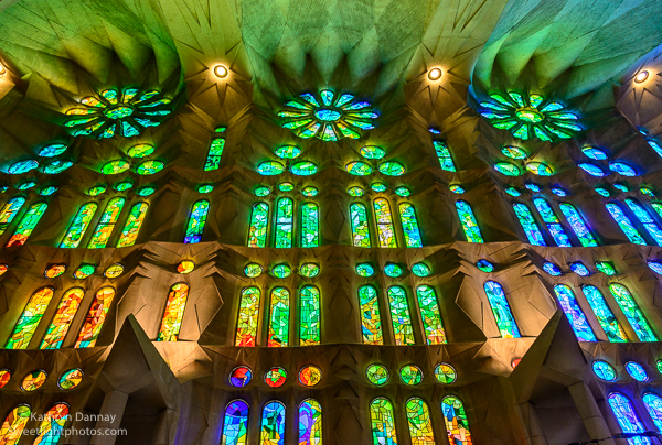 Light streams in through abstract stain glass windows in Sagrada Familia