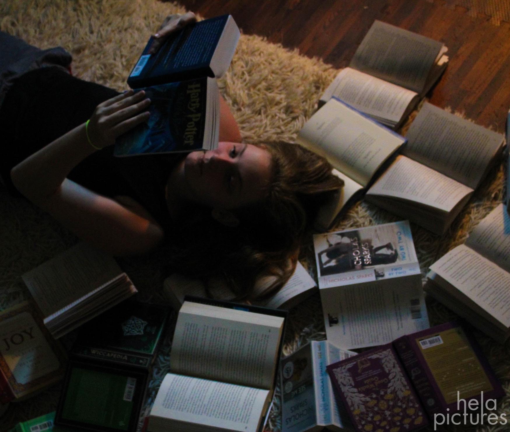 Girl reading books, many books on the floor