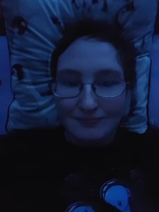 Danni is lying in bed and smiling. The image has a dark blueish hue.