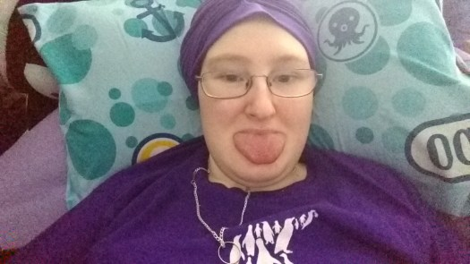 Danni is lying in bed wearing a purple turban. They are sticking their tongue out.
