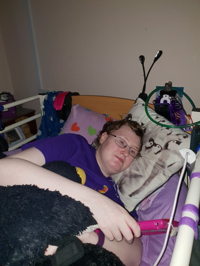 Danni is lying on their side in bed. They look ill.