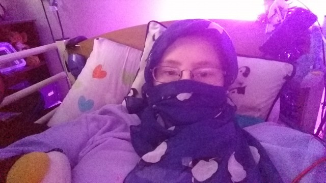 Danni is lying in bed, with a dark blue scarf with penguins on wrapped around their head and lower face. The photo is tinged purple from the light.