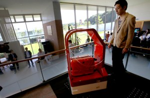 """A porter robot escort a hotel staff during a demonstration for media at Robot hotel """"Henn na Hotel"""" in Sasebo, western Japan, Wednesday, March 15, 2019. (AP Photo/Shizuo Kambayashi)"""