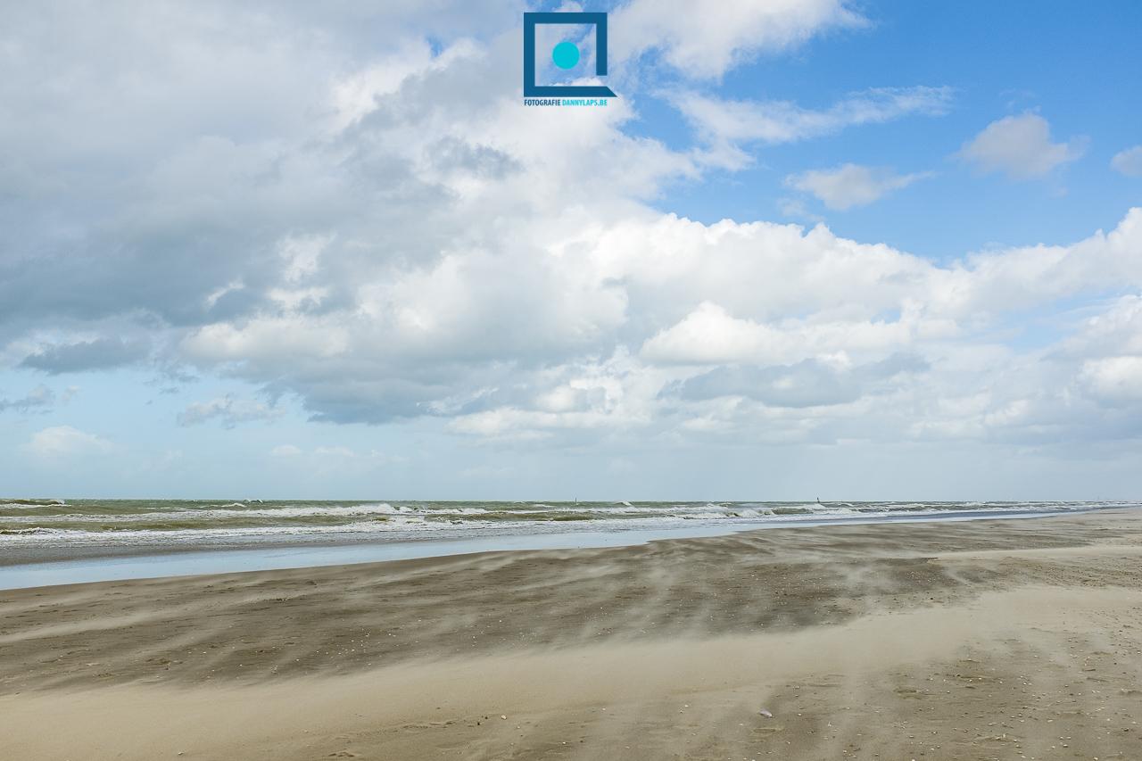Opstuivend zand op het strand met zicht op zee en cumulus wolken.