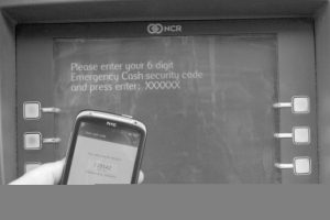 Entering a 6-digit code from a mobile phone into a cash machine.