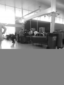 Liz gets her bags searched at airport security.