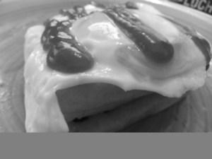 From bottom to top: potato waffle, cheese, potato waffle, egg, tomato ketchup.