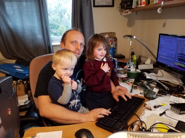 Dan using his computer with John and Annabel on his lap.