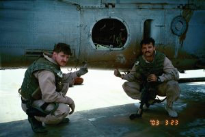 Gash (left) and I pointing out bullet holes in our aircraft, 23 March 2003.  Taken just after we landed from 19 hour flight that culminated in the fight at An Nasiriyah.  pg 163.