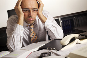 Stressed businessman sitting at desk in office being overloaded