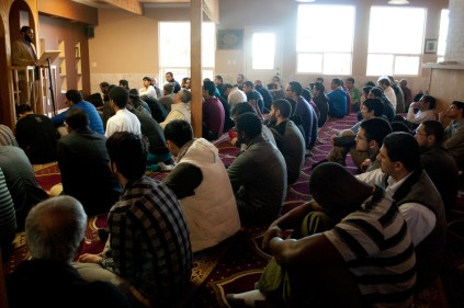 """Mohammad Ahmed (first row, first from left) joins his fellow members of the Muslim Student Association as well as members of his community for """"Jumu'ah"""" – Friday Prayers on Feb. 28, 2014 at the M.S.A.'s Islamic House. The congregational leader – called an """"Imam"""" – delivers a sermon before leading the group in prayer."""