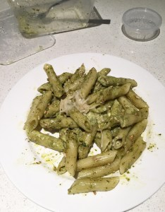plate of penne pesto pasta and parmesan cheese with take away containers all from Basilico